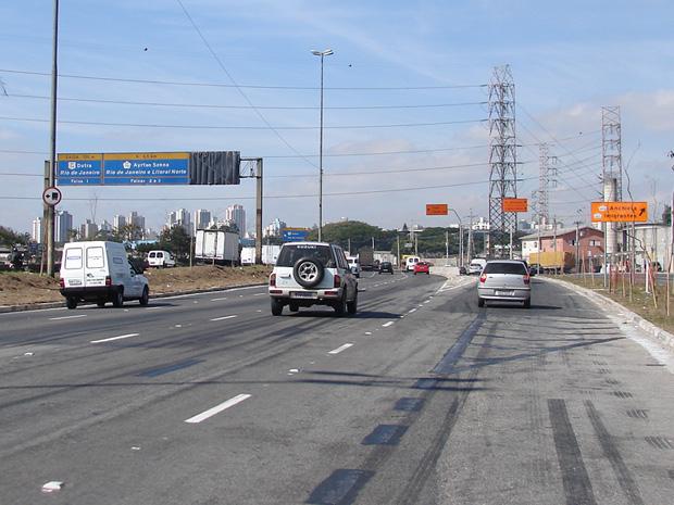 Faixa mal pintada e placa coberta prejudicam tráfego na marginal