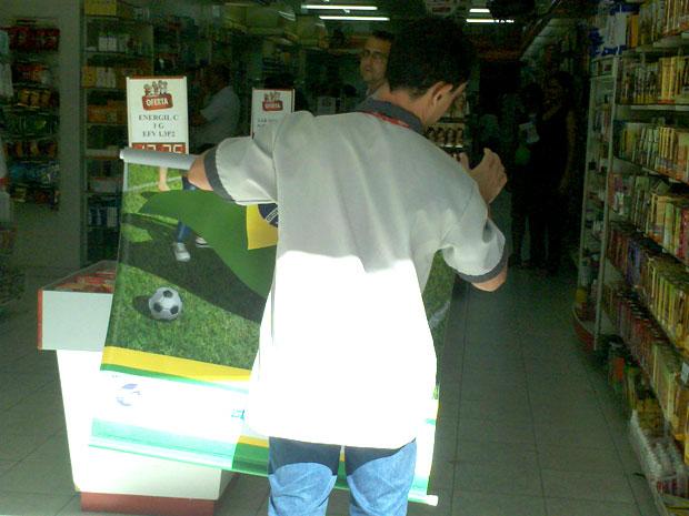 Lojista enrola a bandeira do Brasil que decorava o estabelecimento