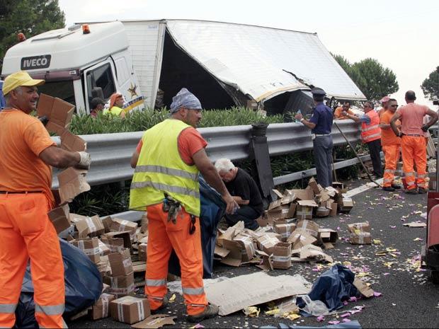 Funcionários tentam recolher moedas que caíram de caminhão