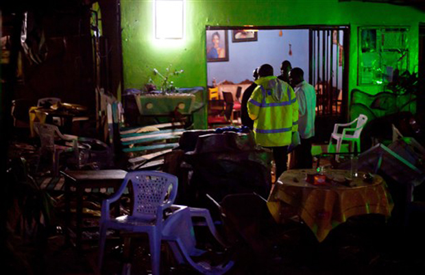 Policiais inspecionam restaurante etíope em Kampala, em Uganda, após explosão que matou pelo menos 15 pessoas na noite deste domingo (11).