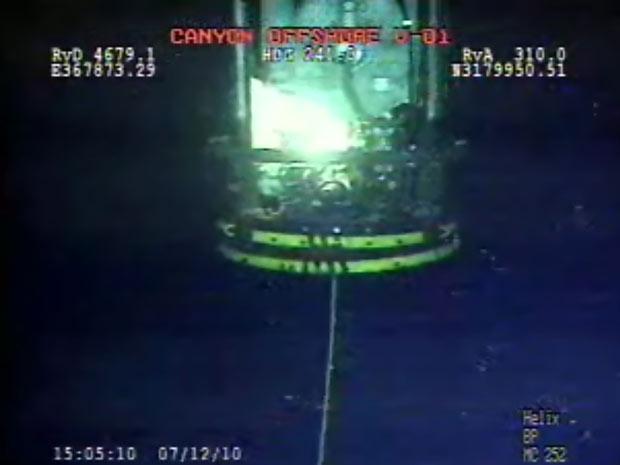 Imagem tirada de vídeo da BP mostra o novo sino de contenção sendo baixado nesta segunda-feira (12), em mais uma tentativa de deter o vazamento de óleo no Golfo do México.