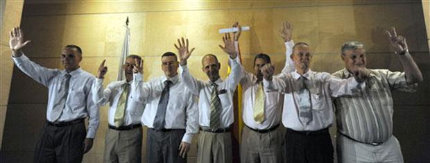 Dissidentes cubanos acenam para jornalistas ao chegarem ao aeroporto de Barajas, em Madri, nesta terça-feira (13).