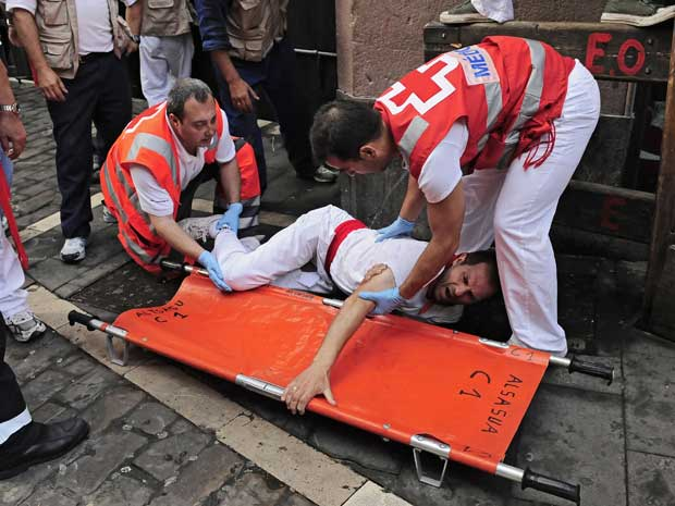 Ferido é socorrido por funcionários da Cruz Vermelha.