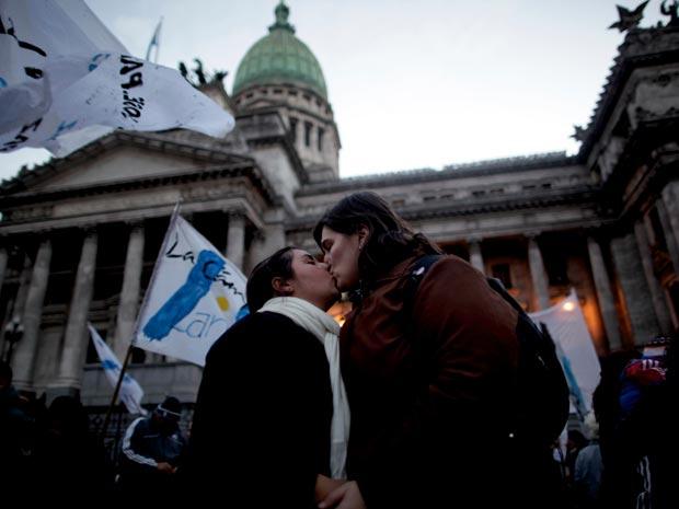 Casal gay beija-se nesta quarta-feira (14) em frente ao Congresso em Buenos Aires, na Argentina.
