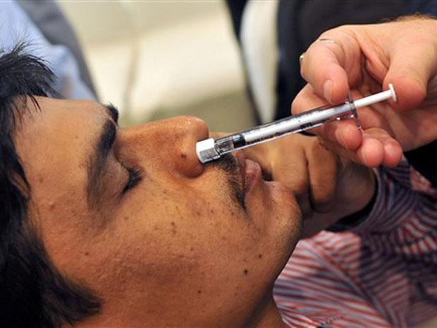 Indiano recebe dose de vacina nasal contra o vírus H1N1, na nova gripe, durante entrevista nesta quarta-feira (14) em Mumbai. A vacina 'Nasovac' foi desenvolvida pelo maior laboratório do país, o Serum Institute, e promete prevenir a infecção. Ela é tomad