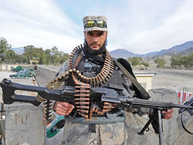Policial da polícia de fronteira afegã mostra armamento em Kunar, dezembro de 2009