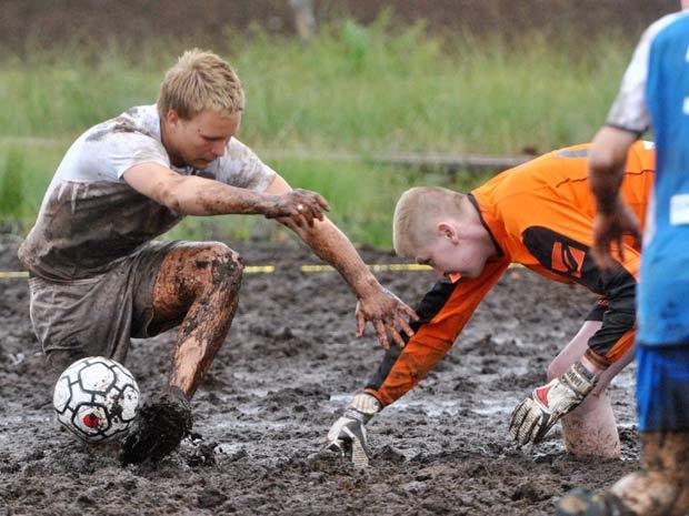Jogadores do Perse Ukot (à esquerda) e do V-alko (em laranja) disputam jogo pelo campeonato internacional de futebol na lama.