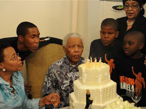 Ao lado de familiares, Mandela assopra velinhas.