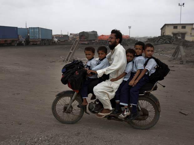 Um motociclista foi flagrado levando cinco crianças em uma moto em Karachi, no Paquistão. O flagra foi feito pelo fotógrafo Akhtar Soomro na última quinta-feira (22).