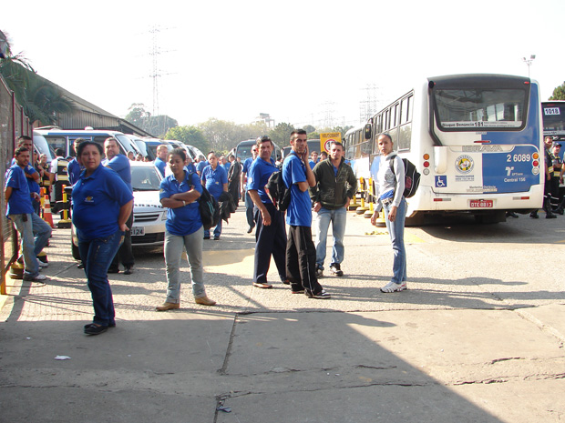 Funcionários e ônibus parados em garagem