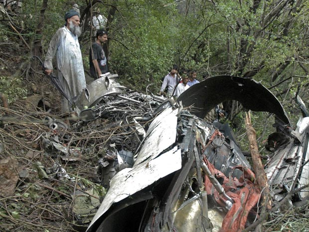 Equipes trabalham entre os destroços do acidente próximo a Islamabad nesta quarta-feira (28).