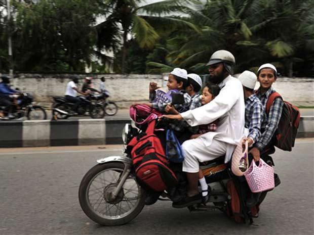 Um indiano foi flagrado nesta quarta-feira (4) em Bangalore, na Índia, carregando cinco crianças, além de mochilas escolares. Nesta quarta-feira, os motoristas de ônibus escolares realizaram uma paralisação.
