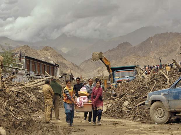 Famílias carregam pertences pela principal avenida de Choglamsar, em Leh, na Índia