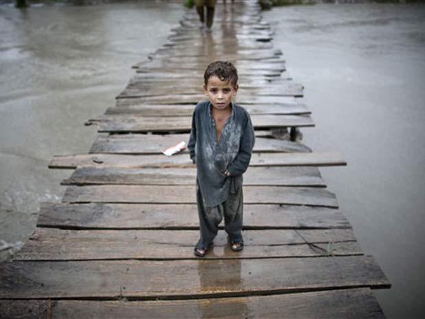 Criança sobrevivente de enchentes caminha por ponte de madeira em Shah Alam, no Paquistão