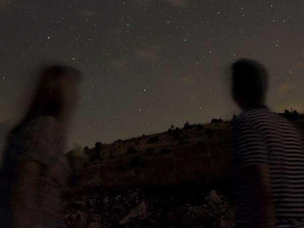 Foto de longa exposição em uma estrada montanhosa ao sul de Skopje, capital da Macedônia, registra os meteoros riscando o céu ao entrarem na atmosfera da Terra.