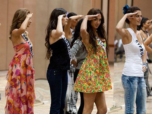 Candidatas ensaiam a batida de continência; Miss Brasil é a de blusa branca e shorts jeans, na foto da direita
