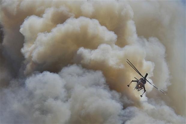 Um helicóptero de combate a incêndios tenta conter um incêndio que começou neste domingo (15) em Vari, subúrbio de Atenas. Fortes ventos e as temperaturas muito altas, de até 40°C, contribuem para o surgimento de novos focos e dificultam trabalho dos bombeiros.