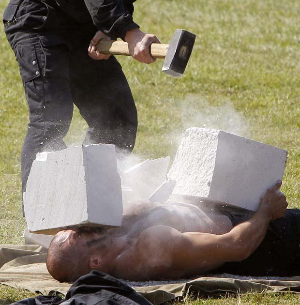 Soldado machão quebra bloco de concreto sobre o peito