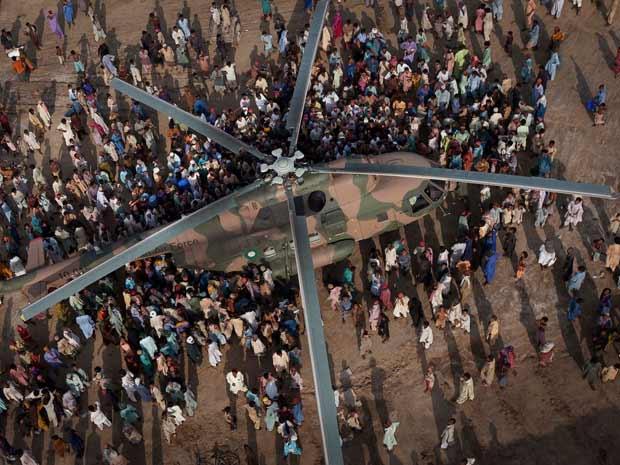 Paquistaneses afetados pelas enchentes que já mataram 1.500 pessoas buscam mantimentos em helicóptero do Exército local