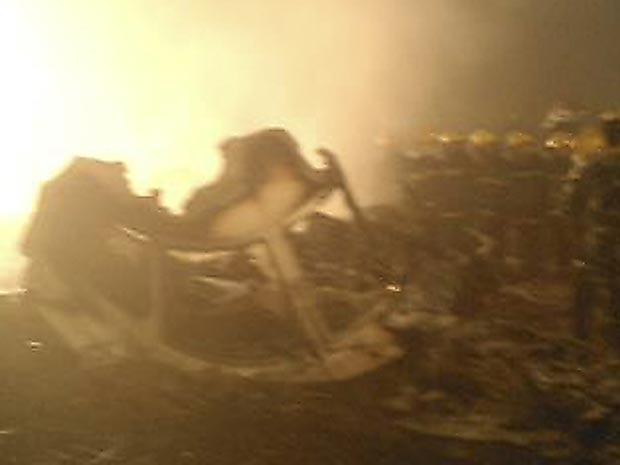 Imagem feita por telefone celular, divulgada pela Xinhua, mostra o avião acidentado nesta terça-feira (24).