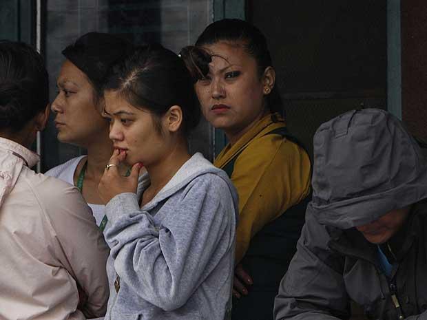 Parentes esperam por informações sobre acidente de avião no aeroporto de Katmandu.
