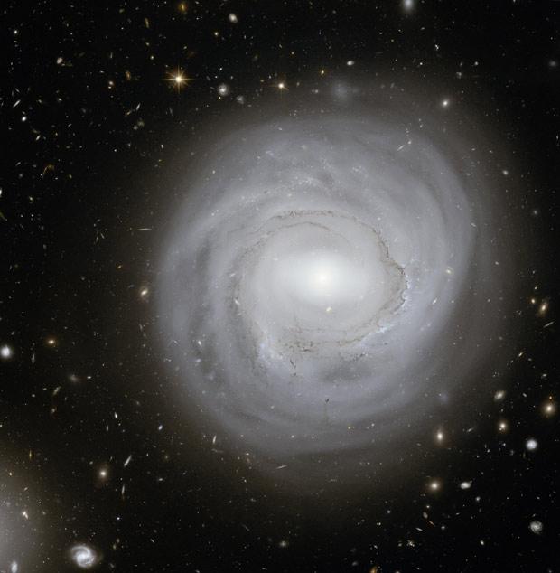 NGC 4921, localizada a 320 milhõe de anos-luz, na direção da constelação de Cabeleira de Berenice. A imagem, feita pelo Telescópio Espacial Hubble, serve aos astrônomos, segundo a Nasa, para identificar marcadores de distância no espaço conhecidos como es