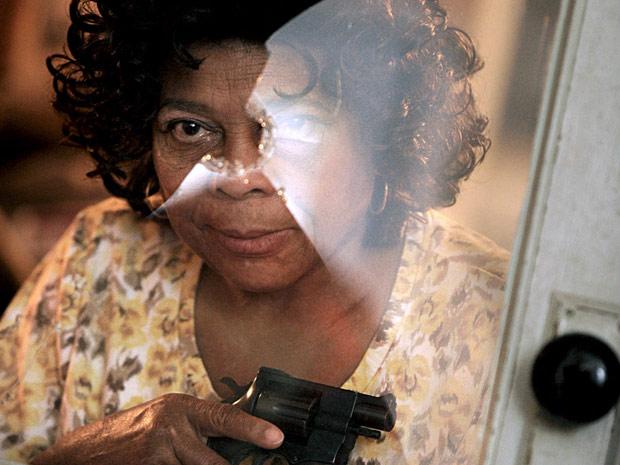 A americana Ethel Jones, de 69 anos, mostra sua arma em frente ao vidro onde uma das balas bateu quando ela disparou três vezes contra um jovem de 18 anos que tentou invadir sua casa no Alabama.