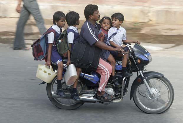 Homem leva quatro crianças em moto na quinta-feira.
