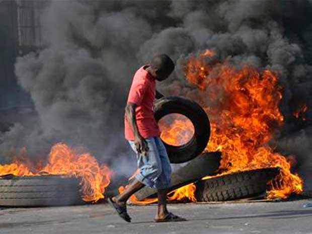 Manifestante joga pneu em uma barricada em chamas durante protestos em Maputo, capital de Moçambique