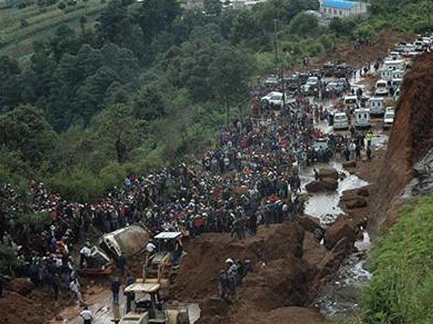 Pessoas se aglomeram ao redor de ônibus soterrado por delizamento de terra em rodovia da capital guatemalteca de Tecpan, neste domingo (5).