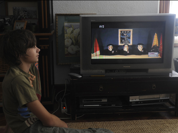 Menino assiste ao anúncio de cessar-fogo de integrantes do ETA em vídeo transmitido pela CNN neste domingo (5), em Guernica, na Espanha