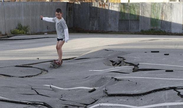 Menino brinca de skate em rua destruída em Paiapoi, 20 km ao sul de Christchurch, cidade mais atingida pelo terremoto na Nova Zelândia