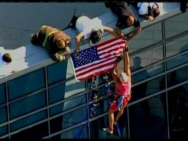 imagens de rede de TV mostram Dan Goodwin afixando uma bandeira americana no topo da chamada Torre do Milênio