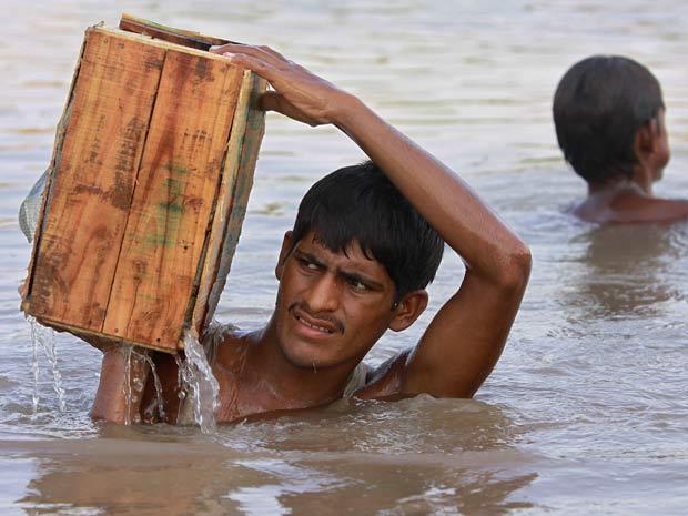 Paquistanês transporta caixa com frutas em região atingida por inundação