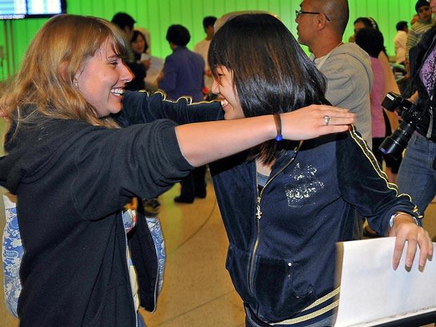 Passageira (à esquerda) é recebida por amiga na noite desta terça-feira (7) após descer do avião que sofreu a ameaça.