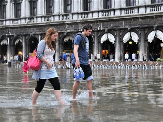 Turistas tiram os sapatos durante enchente na Praça São Marcos, em Veneza, nesta quarta-feira (8).