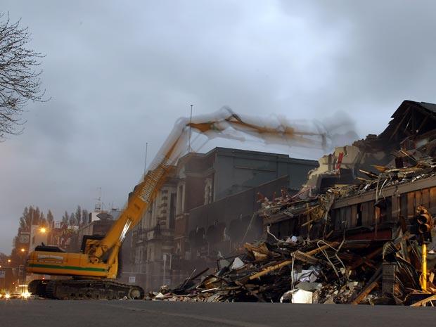 Guindaste derruba nesta quarta-feira (8) restos de prédios destruídos por terremoto na cidade de Christchurch.