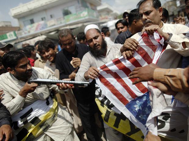 Paquistanês aponta arma de brinquedo contra bandeira dos EUA em protesto em Multan nesta sexta-feira (10).