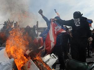 Na capital Santiago, manifestantes queimaram bandeira em atos para lembrar os 37 anos do golpe que derrubou o governo eleito de Salvador Allende