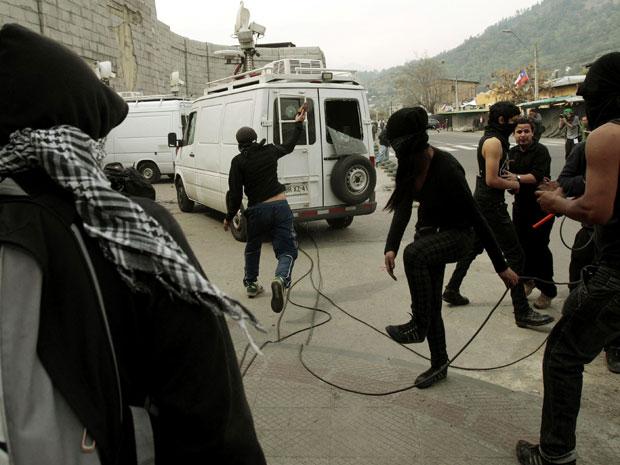 Grupo lança pedras contra veículo de emissora de TV em Santiago, durante ato para lembrar o golpe chefiado pelo general Augusto Pinochet em 1973