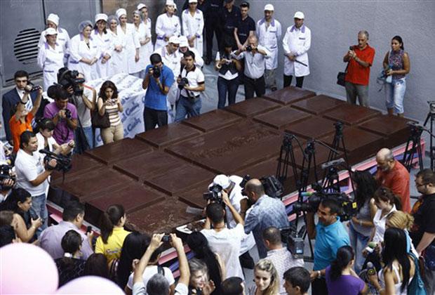 Jornalistas observam barra de chocolate gigante neste sábado (11) na cidade armênia de Yerevan. Uma companhia local afirma ter quebrado o recorde mundial de maior barra de chocolate do mundo. Ela tem 4,41 toneladas e mete 5,6 metros por 2,75 metros, com 25 centímetros de espessura. Ela foi feita usando cacau importado de Gana. O recorde anterior, com uma barra de 3,58 toneladas, havia sido estabelecido em 2007 na Itália.