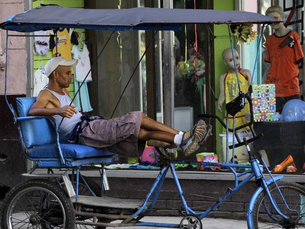 Homem espera por clientes em um triciclo-táxi em Havana: governo promete reduzir burocracia para acelerar licenças para táxi