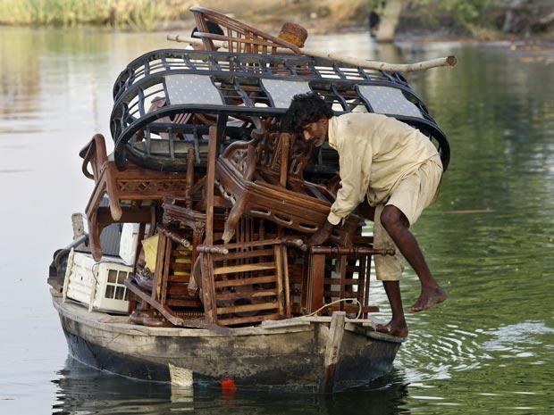 Paquistanês afetado pelas enchentes usa barco para fazer 'mudança' em área alagada no distrito de Dadu, na província paquistantesa de Sindh, nesta quinta-feira (16).