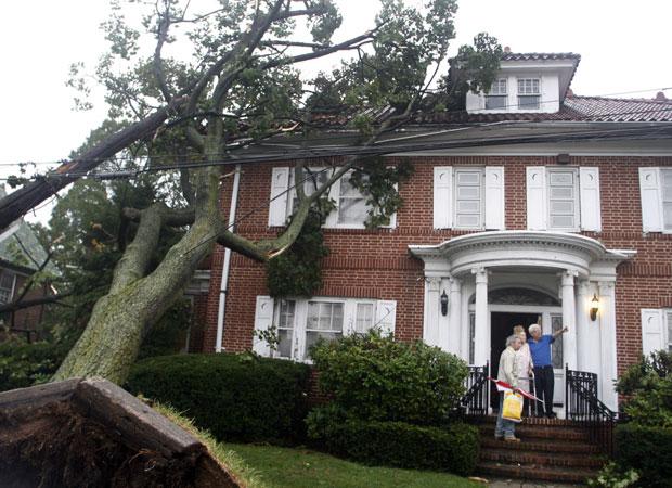 Moradores observam danos causados a casa na Rua 110, em Queens, Nova York, nesta quinta-feira (16).