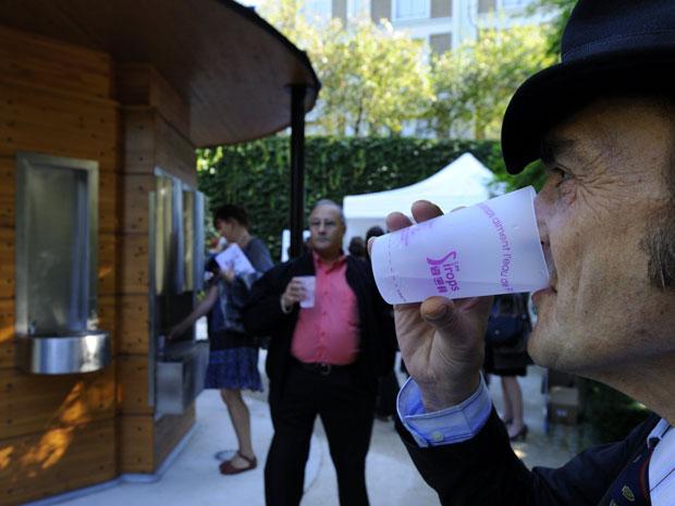 Homem bebe água gaseificada gratuita em fonte pública inaugurada nesta terça-feira (21)