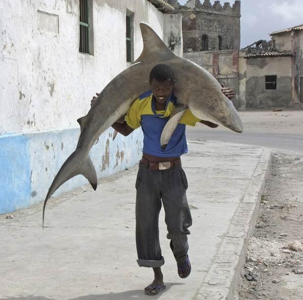 O pescador somali foi flagrado carregando um tubarão em cima dos ombros nesta quinta-feira em Mogadíscio, capital da Somália. O pescador levava o peixe para vendê-lo em um mercado.