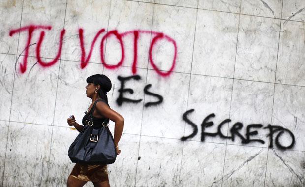 Venezuelana passa em frente de pichação nesta quarta-feira (24) em Caracas.
