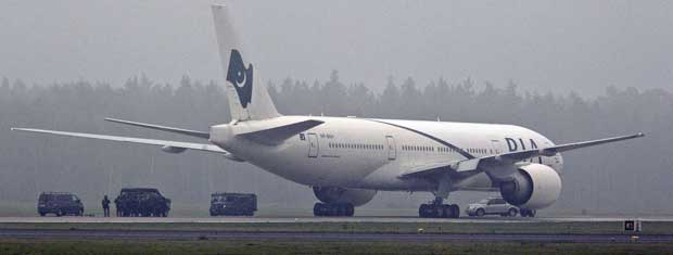 Policiais se aproximam com cautela do avião que mudou a rota e pousou na Suécia por conta de um alerta de que um passageiro pode estar levando uma bomba a bordo.