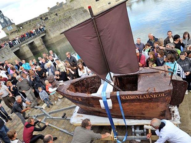 O barco de 3,3 metros é levado pelo fabriocante de chocolates Georges Larnicol no porto de Concarneau