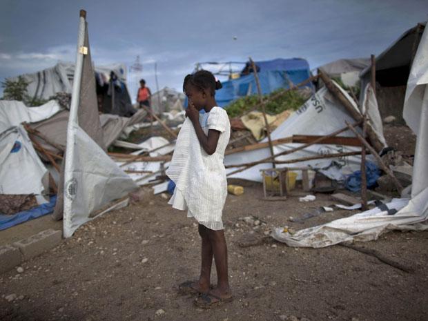 Menina em campo de sobrevivente de terremotos observa os efeitos da chuva em Porto Príncipe